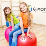 Smiling students sit on gymnastic balls